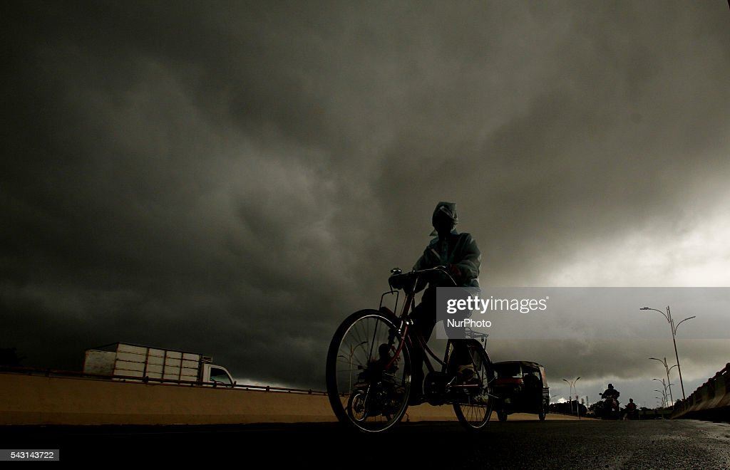 A man wears raincoat and paddles his bicycle on an overpass as monsoon rain clouds hovering in the sky before downpour in the eastern Indian city Bhubaneswar, India, Sunday, 26 June 2016.