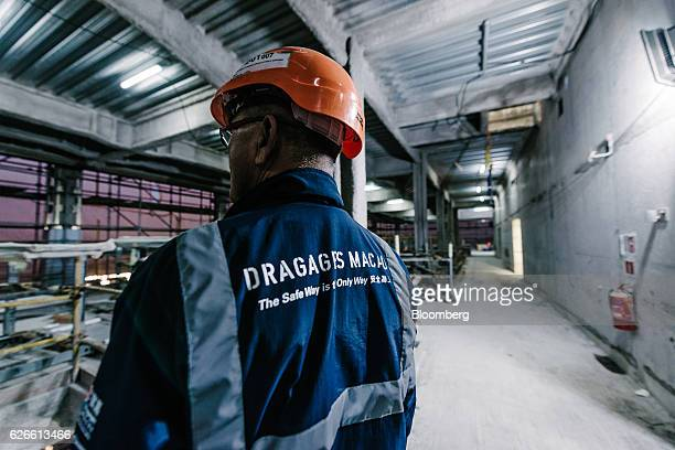 A man wears safety clothing with branding for Dragages Macau Ltd a unit of Bouygues Construction SA at Morpheus Melco Crown Entertainment Ltd's new...