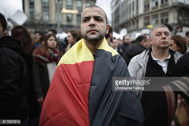 A man wears the Belgian flag as people observe a one minute silence at the Place De La Bourse in honour of the victims of yesterdays' terror attacks...