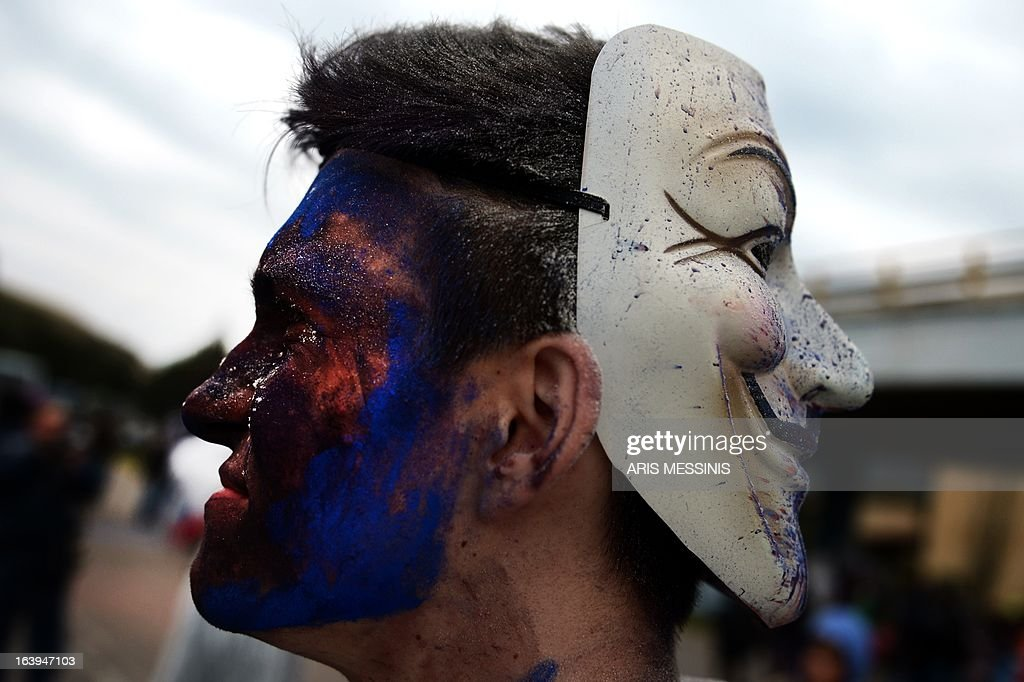 A man wears the Guy Fawkes mask onthe back of his head as people celebrate the annual custom of Flour War in Galaxidi, some 250kms south east of Athens on March 18, 2013.