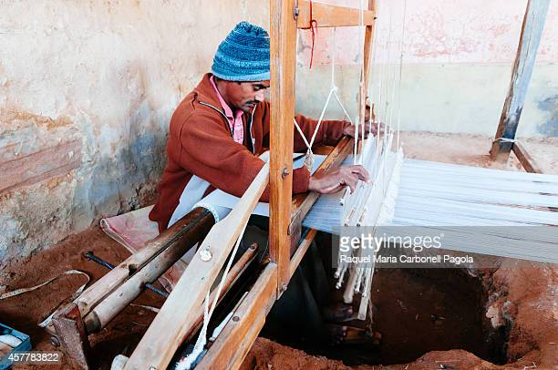 Man weaving with a traditional loom in a village