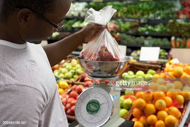 Man weighing apples in supermarket, close-up