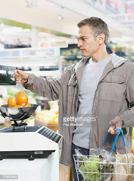 Homme pesant de fruits et de l'épicerie