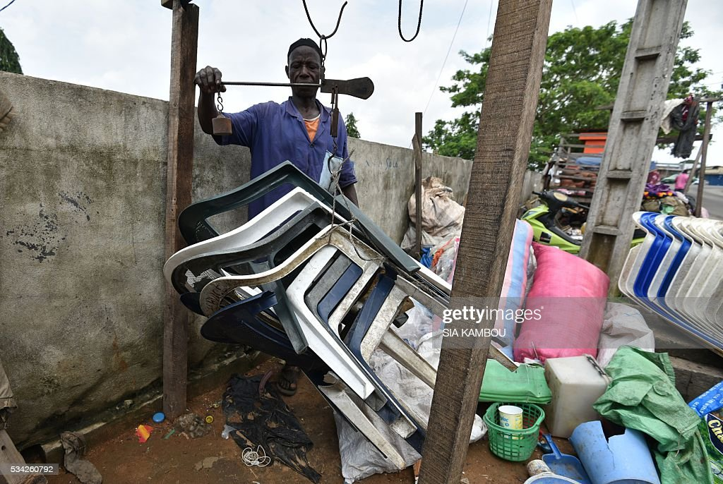 A man weighs plastic chairs used to fabricate cobblestone at a waste repurposing facility on May 23, 2016 in Attecoube, Abidjan. / AFP / Sia KAMBOU