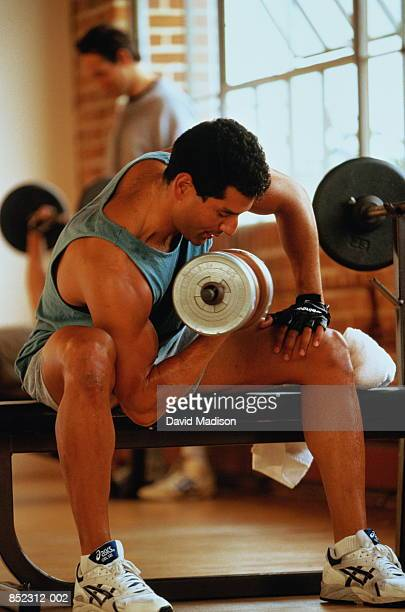 Man weight training with dumbbell in gym