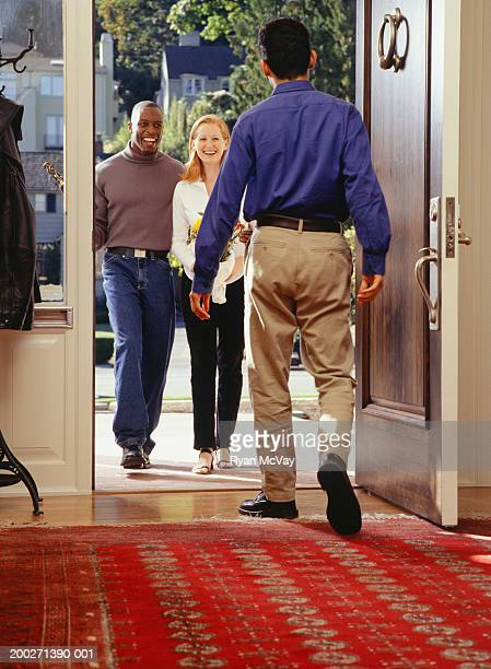 Man welcoming friends at front door into home