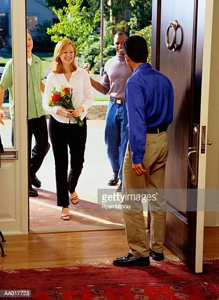 Man Welcoming Friends at His Front Door