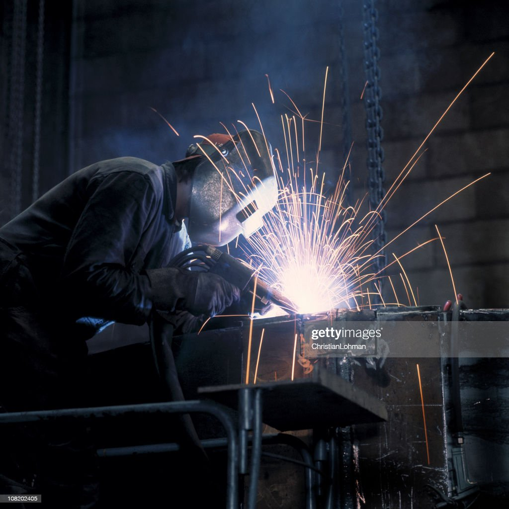 Man Welding in Industrial Warehouse