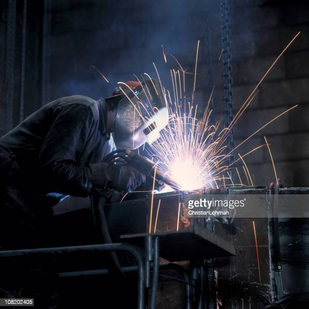 Man Welding in Industrial Warehouse