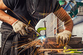 A strong man welder in a black T-shirt, welds a metal welding machine in a welding mask, blue sparks fly to the sides