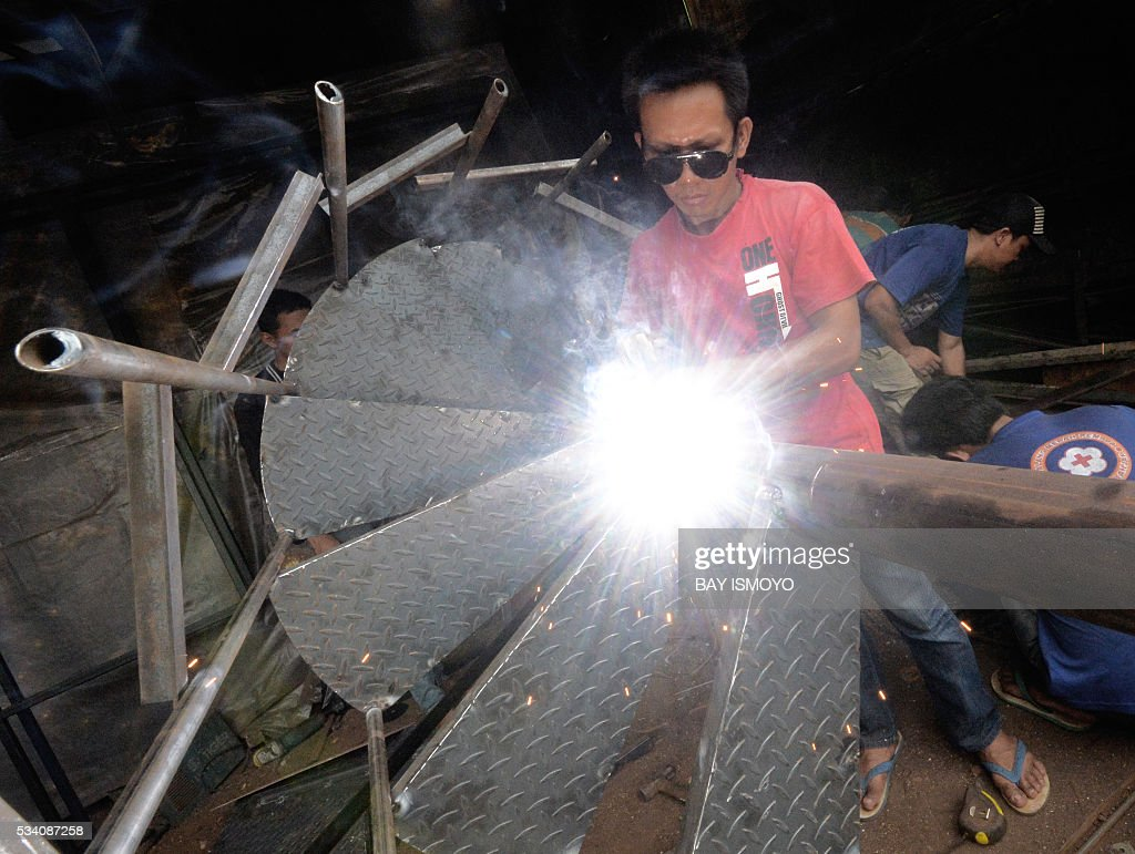 A man welds pieces of a circular stairway together at his workshop in Jakarta on May 25, 2016. Indonesia has opened a string of new sectors to foreign businesses to attract more investment and help pull Southeast Asia's biggest economy out of a slowdown, an official said. / AFP / BAY