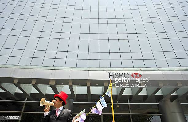 A man weraing a pig nose and holding fake notes shouts slogans during a protest in front of a HSBC branch building in Mexico City on July 30 2012...