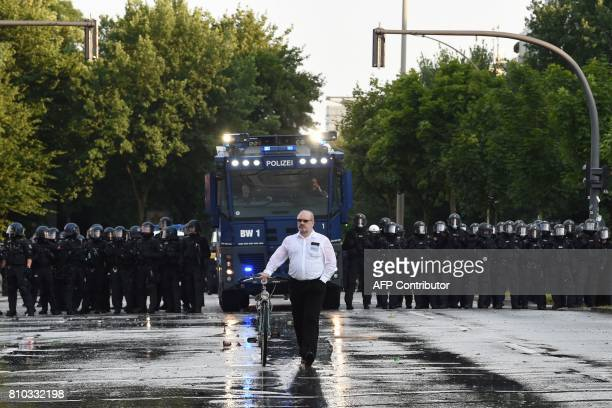 TOPSHOT A man wheels his bicycle in front of riot police with water cannon during a protest on July 7 2017 in Hamburg northern Germany where leaders...