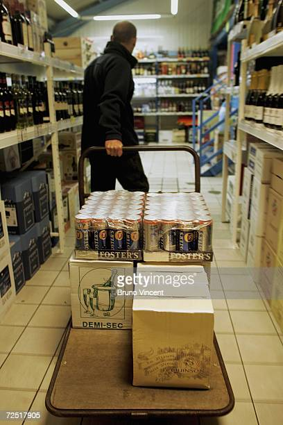 A man wheels his trolley of wine and beer to the check out in a wine warehouse near the Calais ferry port on November 13 2006 in Caliais France A...