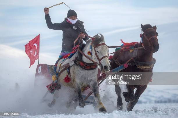 A man whips his horses as he takes part in the horse and sled racing across the frozen Cildir Lake during the Cildir Lake Golden Horse Festival on...
