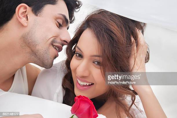 Man whispering in womans ear