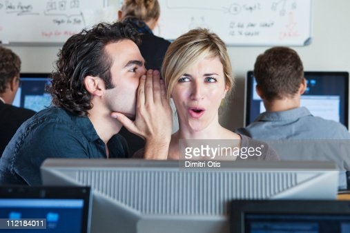 Man whispering into woman's ear in office
