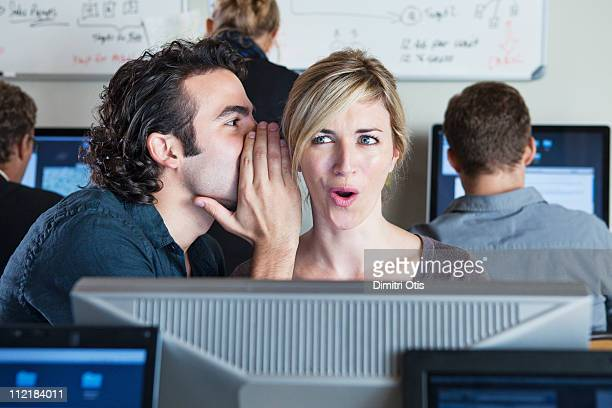 Man whispering into woman's ear in office