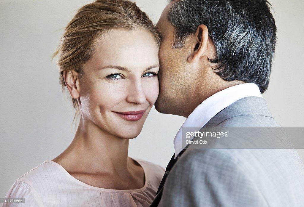 Man whispering to smiling woman : Stock Photo