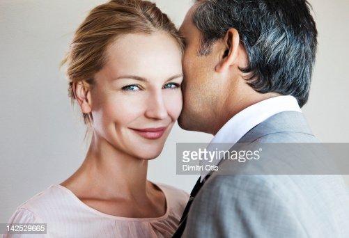 Man whispering to smiling woman