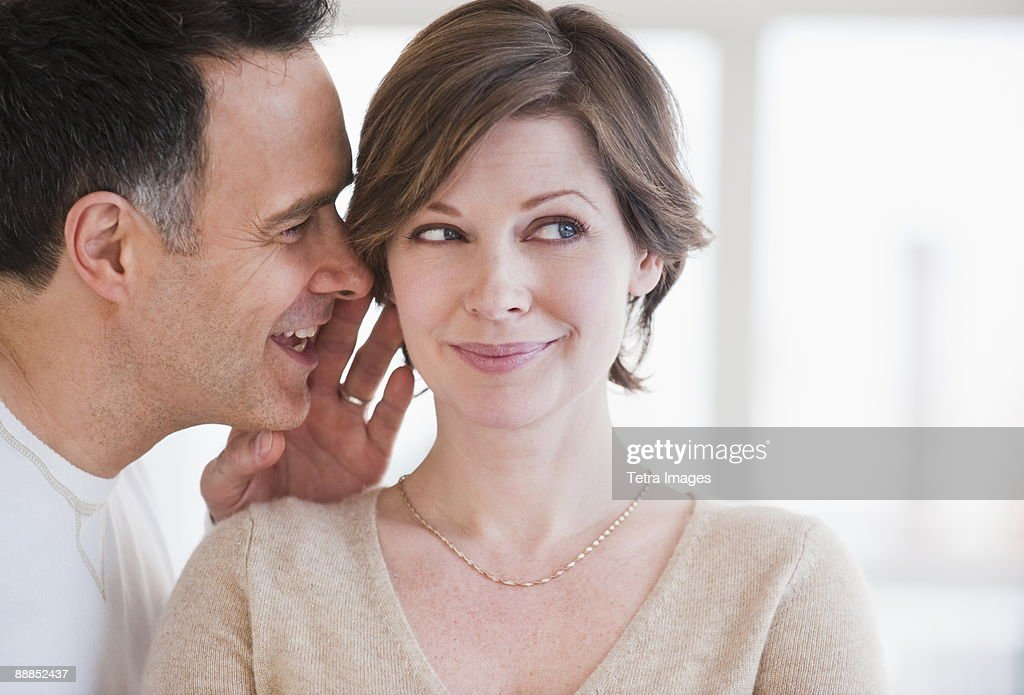 Man whispering to womans ear