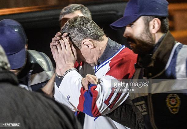A man who attempted to hijack an airliner from Ukraine is escorted by police after the plane was forced down on Febuary 7 2014 at Sabiha Goksen...