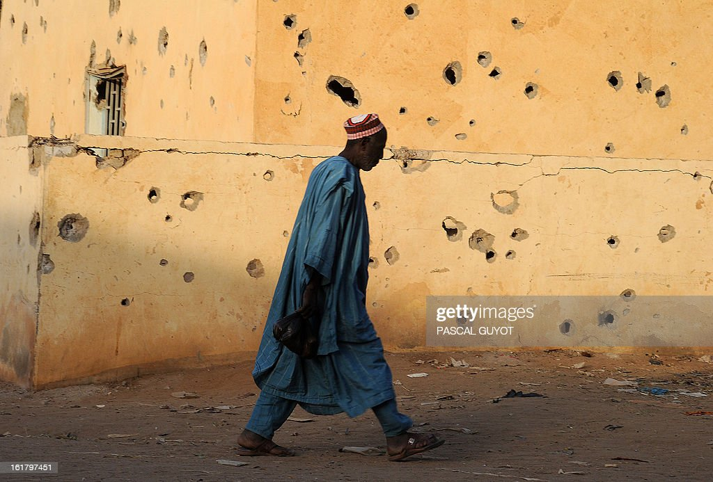 A man who bought food at a market carries past the pockmarked wall of a building on his way home on February 16, 2013 in central Gao, northern Mali. The European Union yesterday announced fresh aid worth 20 million euros to help restore law and order in Mali as well as the return of basic state services such as education after months of trouble. AFP PHOTO / PASCAL GUYOT