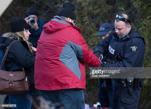 A man who claimed to be from Turkey is handcuffed by the RCMP as his wife watches after crossing the US/Canada border February 27 in Champlain New...
