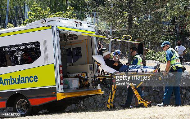 A man who collapsed due to heat is helped by paramedics into an ambulance during a protest for aboriginal rights on November 14 2014 in Brisbane...