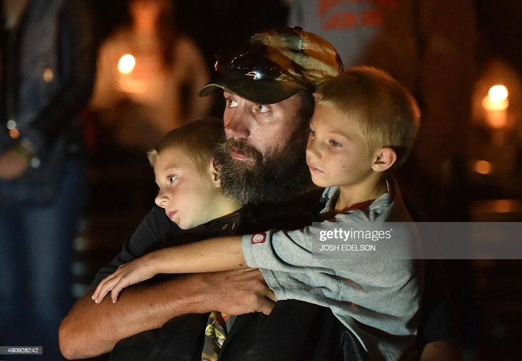 A man who declined to give his name holds his sons during a vigil in Roseburg Oregon on October 1 for ten people killed and seven others wounded in a...