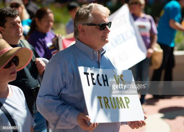 A man who declined to give his name holds up a sign during Tech Stands Up a rally against President Donald Trump in Palo Alto California on March 14...