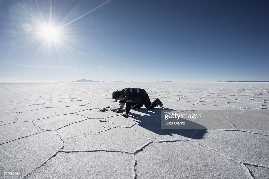 A man who goes by the name Theo digs for salt crystals in the Salar de Uyuni, a flat salt plain that covers just over 4,000 square miles and lies at 12,000 ft above sea level in UYUNI, BOLIVIA. Theo has been hunting these salt crystals for 15 years mostly as gifts for his family who then barter them for food and clothes in the Uyuni market some 40 miles away. The expansive and ethereal flats were formed as a result of transformations between several prehistoric lakes. It is covered by a few meters of salt crust that serves as a source of household salt and covers a pool of brine, which is exceptionally rich in lithium. The Uyuni flats contains 50 to 70% of the world's lithium reserves, which is in the process of slowly being extracted.