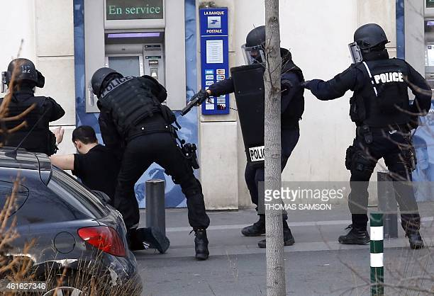 A man who had taken two hostages in a post office is arrected by French Research and Intervention Brigades police officers on January 16 2015 in...