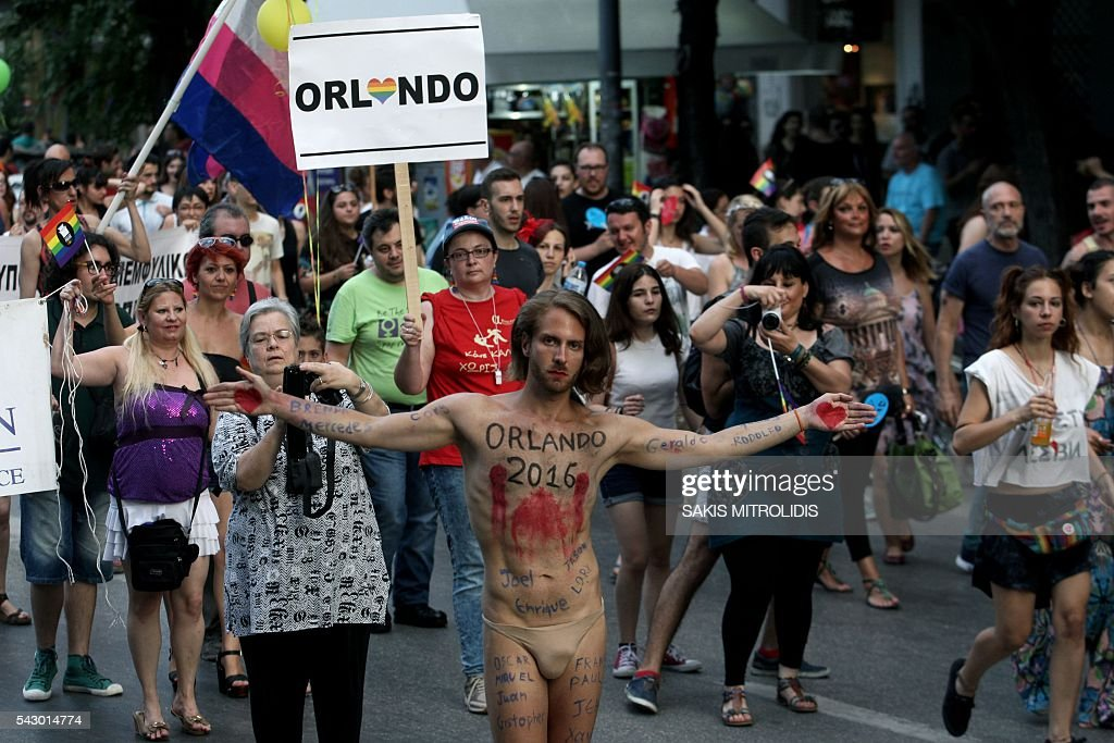 A man who has written on his body the names of the victims of Orlando's gay bar shooting walks with thousands of people in the streets of Thessaloniki, northern Greece, during the city's 5th Gay Pride march, on June 25, 2016. / AFP / SAKIS