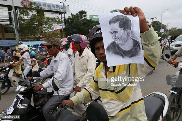 A man who holds portrait of slain prominent political analyst Kem Ley during a funeral procession to mark 100 days since his death Kem Ley was shot...
