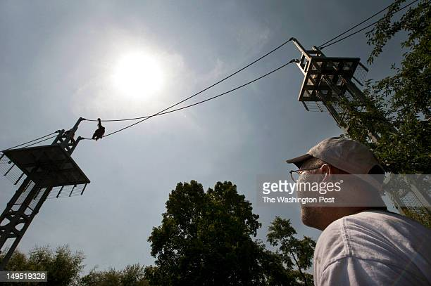 A man who identified himself only as Mike watches an orangutan cross the O Line at the Smithsonian National Zoological Park on Thursday July 05 2012...