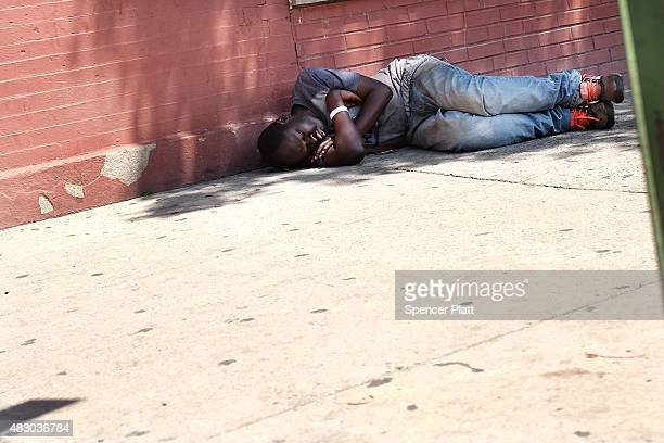 A man who is high on K2 or 'Spice' a synthetic marijuana drug sleeps along a street in East Harlem on August 5 2015 in New York City New York along...