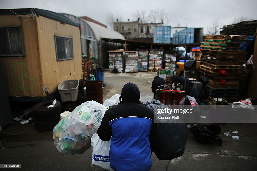 A man who makes a living by collecting bottles and cans or 'canning' for short, pushes an evenings collection into Sure We Can, a non-profit bottle redemption center in Bushwick, Brooklyn that is pushing to become a cooperative for the canning community on February 16, 2013 in New York City. Sure We Can, which was partly started by homeless canners in 2007 and is run by one of its founders Sister Ana Martinez de Luco, looks to give the diverse members of the canning community a safe and fraternal place to redeem cans, store their carriages and become members of an association that encourages self-dependence and responsibility. Many of New York's canners are non-English-speaking elderly immigrants who live a marginalized existence and are vulnerable to dishonest business practices. Sure We Can currently serves around 50 canners per day and recycles over 6 million bottles and cans per year.