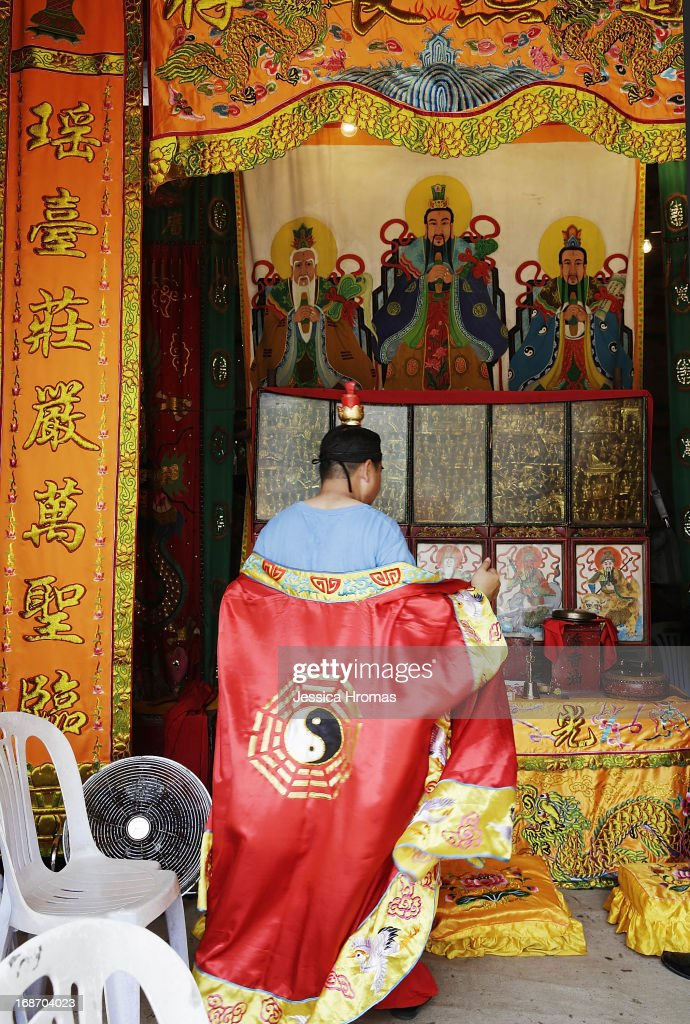 A man who participated in the ceremony inviting Tin Hau to Pak Tai Temple, prays at a shrine, on the first day of the Cheung Chau Bun Festival, Cheung Chau Island on May 14, 2013 in Hong Kong, Hong Kong. Today is the start of the Cheung Chau Bun Festival which will run until 17 May and celebrates the eight day of the fourth moon in the Chinese calendar.