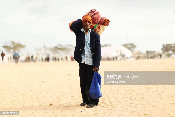 A man who recently crossed into Tunisia from Libya waits for friends at a United Nations displacement camp on March 08 2011 in Ras Jdir Tunisia As...