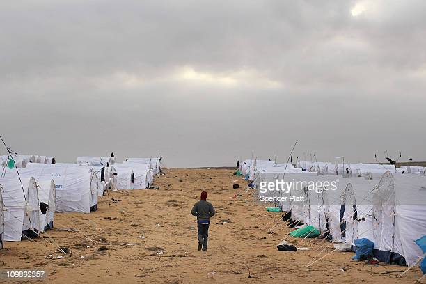 A man who recently crossed into Tunisia from Libya walks among tents in a United Nations displacement camp on March 08 2011 in Ras Jdir Tunisia As...