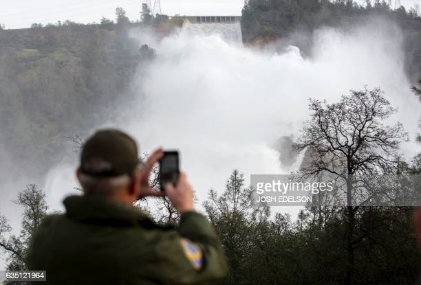A man who works for the California Department of Fish and Wildlife takes a photo with his phone of rushing water as it is released down a spillway at...