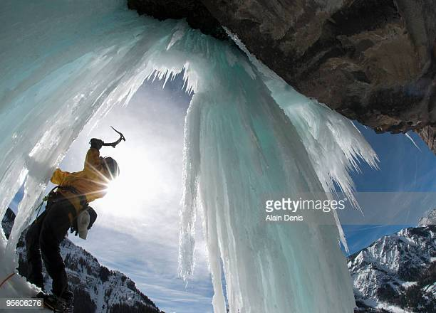 A man wields his ice ax while ice climbing a frozen waterfall near Ouray, Colorado. (solar flare)
