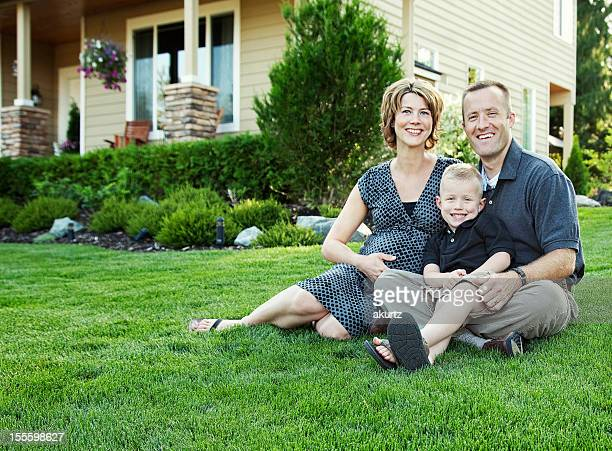 Man, wife and child outside of family house
