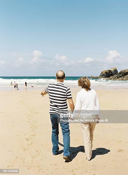 man & wife walk along the beach