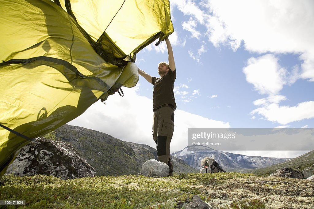 Man wildcamping, setting up tent : Stock Photo
