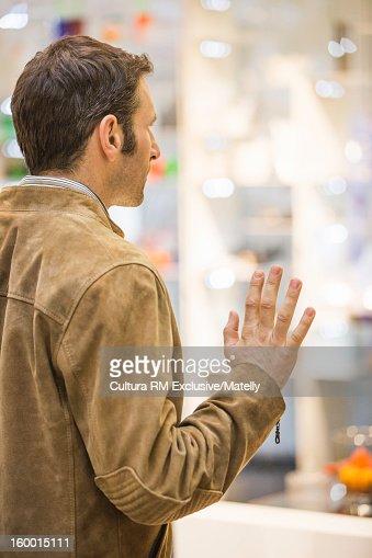 Man window shopping on city street