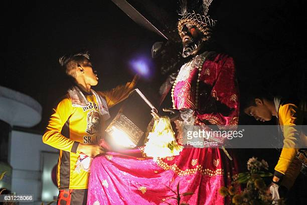 GRANDSTAND MANILA NCR PHILIPPINES A man wipes a towel at a replica image of the Black Nazarene This practice is part of tradition of venerating the...