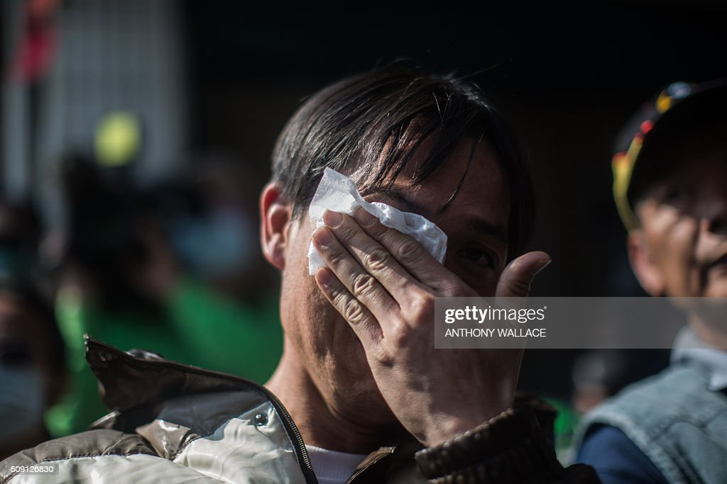 A man wipes away tears after asking a question during a briefing to relatives by Tainan's Mayor William Lai and Cheng Ming-chang, president of Tainan civil engineers association (both not seen), on the rescue operation of a building which collapsed in the 6.4 magnitude earthquake, in the southern Taiwanese city of Tainan on February 9, 2016. Rescuers deployed heavy machinery on February 9 in a renewed effort to locate more than 100 people trapped in the rubble of a Taiwan apartment complex felled by an earthquake as the 72-hour 'golden window' for finding survivors passed. AFP PHOTO / ANTHONY WALLACE / AFP / ANTHONY WALLACE