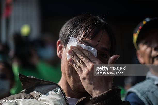 TOPSHOT A man wipes away tears after asking a question during a briefing to relatives by Tainan's Mayor William Lai and Cheng Mingchang president of...